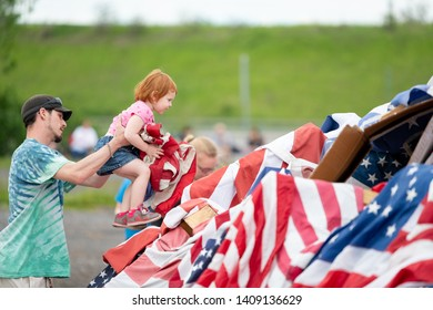 Syracuse, New York/USA - May 26,2019:A father helps his very young daughter place an American flag on a pile of flags at the Watch Fire Ceremony.