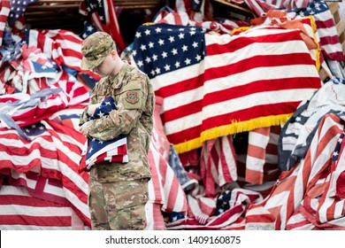 Syracuse, New York/USA - May 26,2019:A Soldier Cradles the American Flag near a pile of flags at the Watch Fire Ceremony