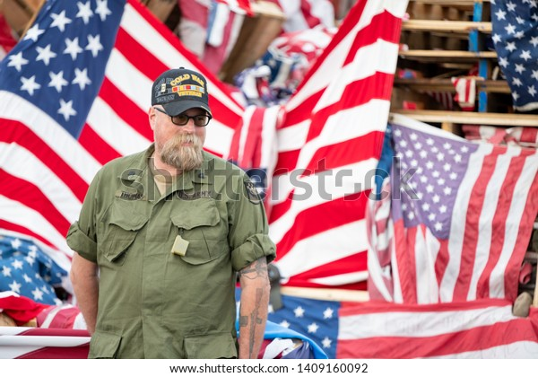 Syracuse, New York/USA - May 26,2019:A Veteran poses for a picture in front of a pile of United States Flags at the Watch Fire Ceremony.