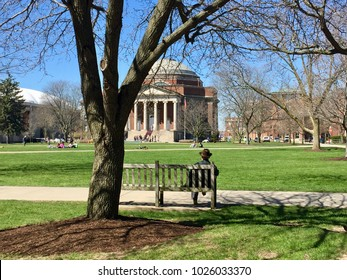 SYRACUSE, NY - APRIL 20, 2016: A man sits on a bench in Syracuse University campus with a view to Hendricks Memorial Chapel in Syracuse, New York.