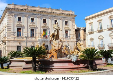 Syracuse, Sicily, Italy - Apr 10th 2019: Beautiful Fountain of Diana on the Archimedes Square in famous Ortigia Island. Building of a Sicilian bank in the background. Sunny day, blue sky.