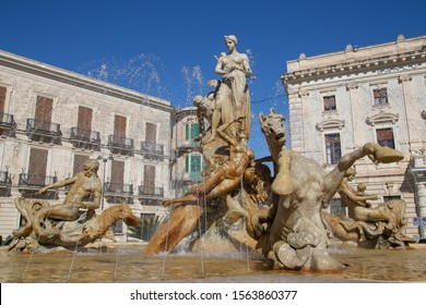 Syracuse, Sicily, Italy - March 13, 2018: View of the Fountain of Diana in Archimedes Square in Ortigia. Built by Giulio Moschetti in 1907, this classic fountain features a statue of the goddess Diana