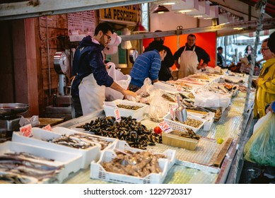 SYRACUSE, SICILY / ITALY - OCTOBER , 2018:  People walking in Ortigia fresh food street market. Sea food seller and his clients