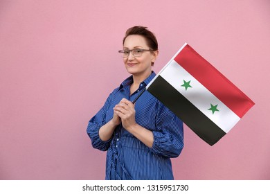Syria flag. Woman holding Syrian flag. Nice portrait of middle aged lady 40 50 years old holding a large flag over pink wall background on the street outdoors.