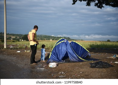 A Syrian refugee watches his son as he plays outside their tent at the makeshift refugee camp of Idomeni at the Greek - Macedonian border.