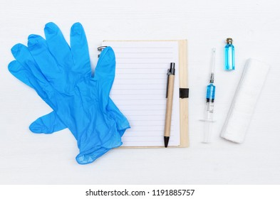 Syringe, blank page notepad, bandage and ampoule with blue liquid drug on the doctor table. Medical journal or doctor prescription mockup.