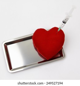 Syringe injecting a red heart on aluminum tray.