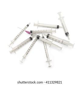 Syringe with needle on top of used syringes on white background