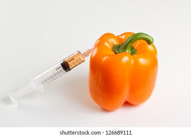 syringe with orange liquid next to a sweet pepper representing gmo, genetically modified organism or food