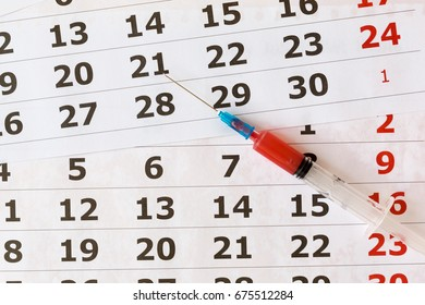 Syringe with red blood on a calendar