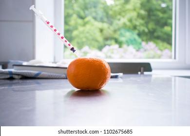 Syringe sticked into orange on wooden table,GMO