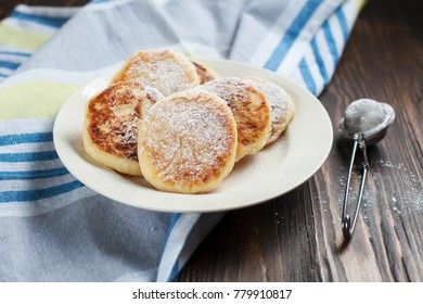 syrniki with powdered sugar on a white plate, sieve, towel on a dark, wooden table