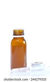 Syrup bottle with syringe on white background.