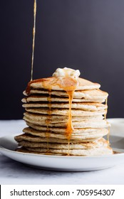 Syrup is poured down a tall stack of golden pancakes layered on a gray plate with melted butter and syrup dripping down the sides of the stack.
