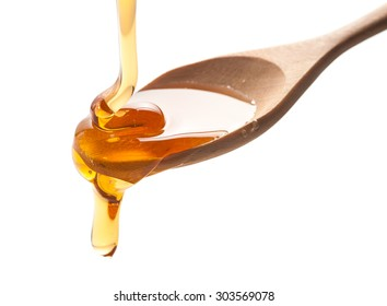 syrup pouring on spoon on white background