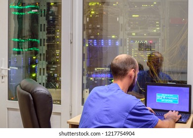 System administrator with a laptop sits in front of the glass door of the server room. The programmer works in a modern data center. The concept of providing telecommunications services.