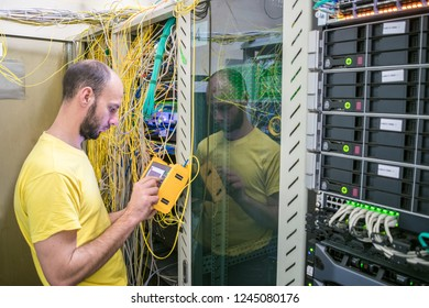 The system administrator is testing the network with a reflectometer. The man works in the server room of the datacenter. A technician measures the signal level in a fiber optic cable.
