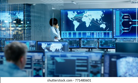 In the System Control Room Chief Engineer Thinks While Standing Before Big Screen with Interactive Map on it. Data Center is Full of Monitors Showing Graphics.
