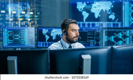 System Control Room Dispatcher Talks into Headset. He Controls Correct Work of the Facility. In the Background Multiple Monitors Show Technical Data.