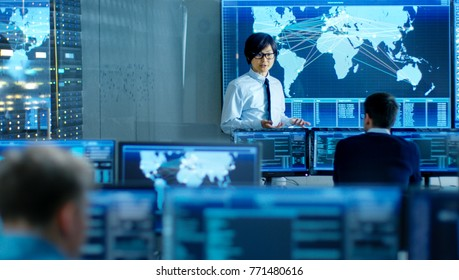 In the System Control Room Manager Holds a Briefing for His Staff Members. They're Work in Data Center and are Surrounded by Multiple Screens Showing Maps, Logistics Data.