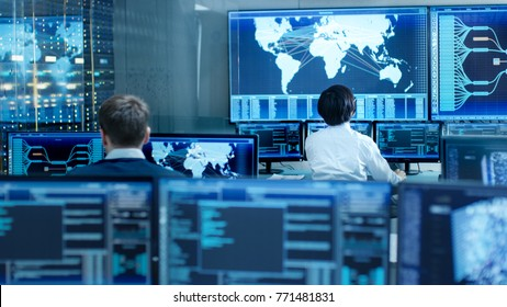 In the System Control Room Operator and Administrator Sitting at Their Workstations with Multiple Displays Showing Graphics and Logistics Information.