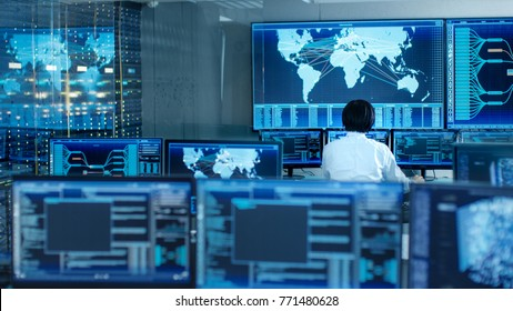 In the System Control Room Operator Sits at His Workstation with Multiple Displays Showing Graphics and Logistics Information.