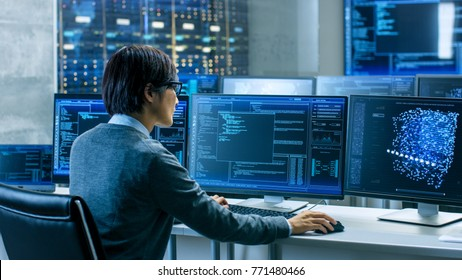 In the System Control Room Technical Operator Works at His Workstation with Multiple Displays Showing Graphics. IT Technician Works on Artificial Intelligence, Big Data Mining, Neural Network Project.