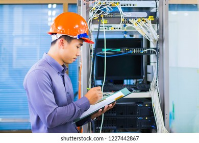 A system engineer who is monitoring hardware and software security in the server room for data security in the company.