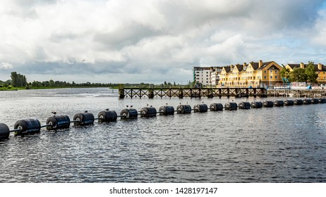 System of lock, weir and sluice gates in the Shannon river with black buoys in Athlone town, wonderful days in the county of Westmeath, Ireland