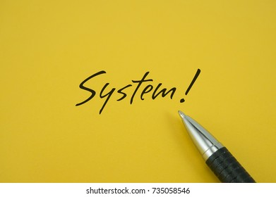 System! note with pen on yellow background
