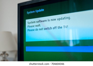 System update software process on a modern television set in living room with message System software is now updating, please wait. Please do not switch off your tv. Tilt-shift lens used