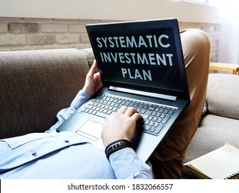 Systematic Investment Plan SIP. The man is reading on a laptop.