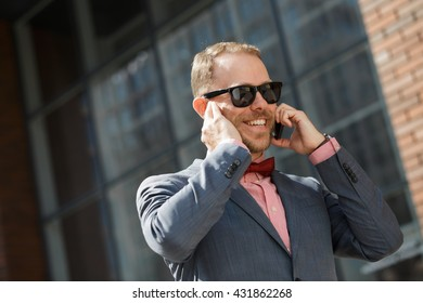 Sytlish businessman in sunglasses speak by smartphone at city downtown