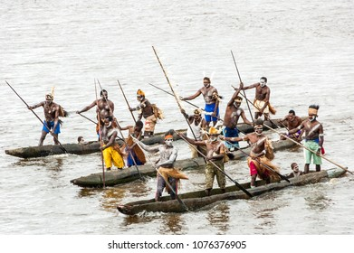 Syuru, Asmat Region/ Indonesia - November 9 2012: When a ship visits, the warriors of the village make a mock attack in canoes, before allowing the passengers to come ashore and visit the village