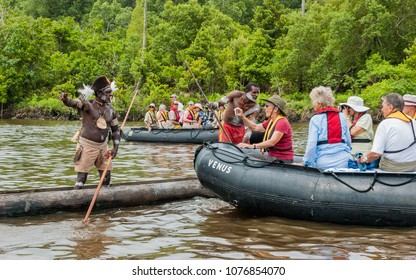 Syuru, Asmat Region/ Indonesia - November 9 2012: As part of the ritual welcome, visitors from a ship are first blocked by war canoes, and then formally invited to the village