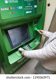 Syzran, Russia - June 20 , 2018: finance, money, bank and people concept - close up of hand taking receipt from atm machine of the Sberbank