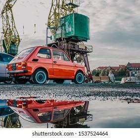 """Szczecin, Poland - 20.10.2019: small fiat 126p """"maluch"""" near the big yellow cranes in szczecin"""