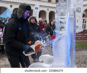 SZCZECIN, POLAND -  DECEMBER 6, 2014: Unidentified man with chainsaw Stihl, creating artwork out of the block of ice. Stihl is a German manufacturer of chainsaws and other power equipment.