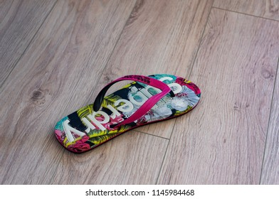 Szczecin, Poland - July 14, 2018: Colorful Superdry shower shoe left on a wooden table