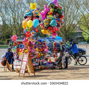 Szczecin, Poland - May 03, 2015: Person by a stand selling helium balloons at a park on a warm spring day