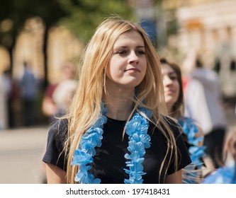 SZCZECIN, POLAND - MAY 23, 2014: Juwenalia, is an annual students' holiday in Poland, usually celebrated for three days in late May. Beautiful blonde girl with Hawaiian garlands watching performances.