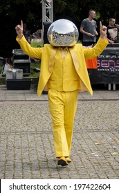 SZCZECIN, POLAND - MAY 23, 2014: Juwenalia, is an annual students' holiday in Poland, usually celebrated for three days in late May. Disco Ball Man in a yellow dress, dancing in the street.