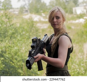 SZCZECIN, POLAND - MAY 31, 2014: Beautiful sexy blond woman holding army weapon, during historical reconstruction