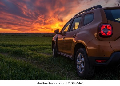 Szczecin,Poland-April 2020: Dacia Duster SUV standing on a dirt road during a spectacular sunset