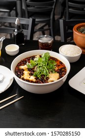 Szechuan food in a restaurant. Spicy Sichuan fish soup made with pungent chili peppers and fresh cod. Authentic and fiery Chinese food.