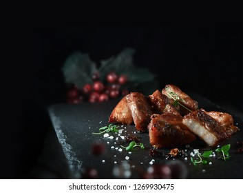 Szechuan pork grilled with traditional Chinese spices, prepared for serving with a thyme herb garnish. The perfect image for your fine dining cover art menu designs. Copy space.