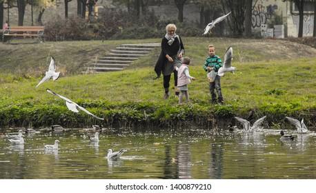 Szeged, Hungary, circa 2018. 11. 01. Grandmom and grand children feeding seagulls at a local lake of Szeged.