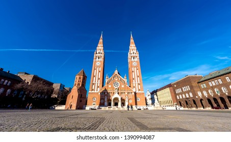 SZEGED, HUNGARY - CIRCA APRIL 2019: View on the famous Cathedral as visitors pass by at the church circa April 2019 in Szeged, Hungary.