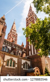 Szeged, Hungary - June 18, 2013: The tower of the Votive Church with clock from below. The Votive Church and Cathedral of Our Lady of Hungary is a twin-spired church in Szeged.