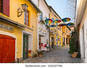 SZENTENDRE, HUNGARY - MARCH 17, 2019: Colorful buildings and umbrellas on a narrow cobblestone street leading to Danube Promenade in Szentendre